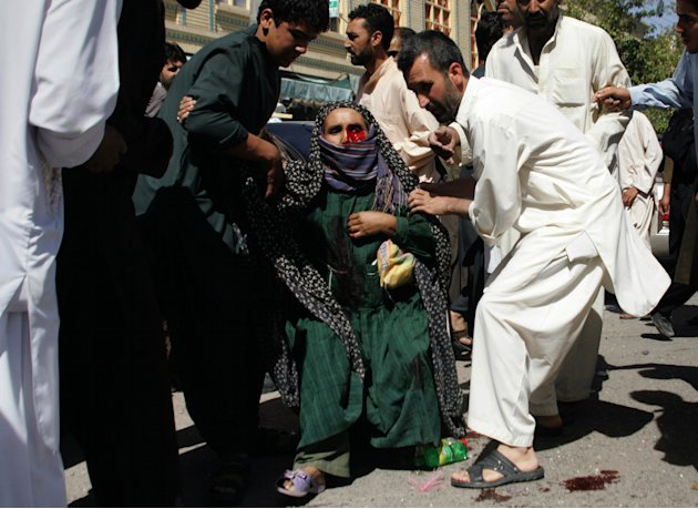 Afghans carry a wounded woman from the scene of an explosion in Herat, west of Kabul, Afghanistan, Wednesday, Aug. 15, 2012. Over a dozen people, including four women and a policeman, were injured whe