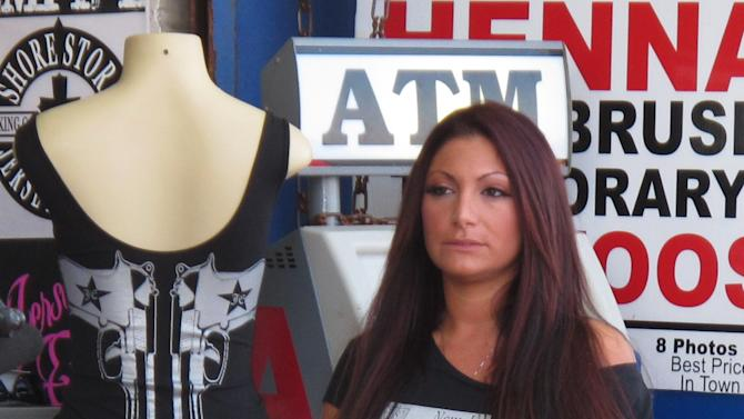 """In this June 8, 2012 photo, """"Jersey Shore"""" cast member Deena Cortese takes a break from filming the MTV reality show on the boardwalk in Seaside Heights, N.J. New Jersey liquor regulators said Thursday, Sept. 13, 2012 that they have fined the Seaside Heights restaurant Spicy Cantina & Mexican Grill $15,000 for serving alcohol to a """"visibly intoxicated"""" Cortese on June 10, just before she wandered out into traffic and was arrested. As a condition of the agreement, Cortese is banned from the cantina's premises for two years. (AP Photo/Wayne Parry)"""