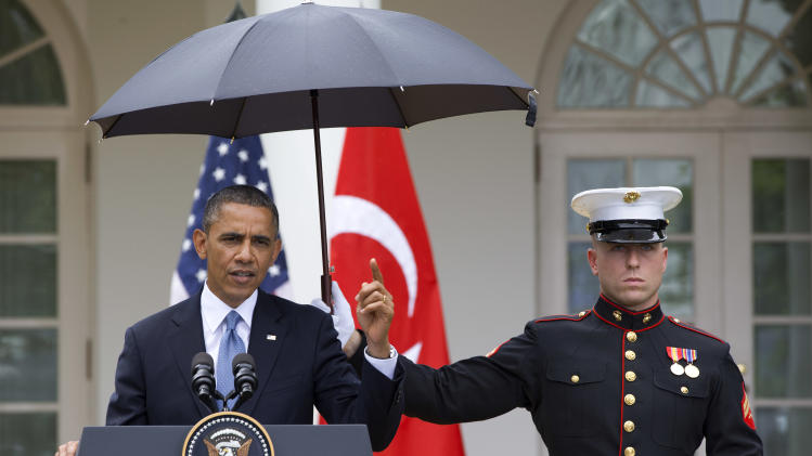 President Barack Obama speaks under an umbrella held by a Marine as a light rain falls during a news conference with Turkish Prime Minister Recep Tayyip Erdogan, Thursday, May 16, 2013, in the Rose Garden of the White House. (AP Photo/Jacquelyn Martin)