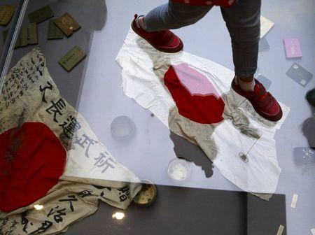 A visitor walks on a glass flooring above Japanese military flags seized by the Chinese PLA during World War Two, at the Museum of the War of Chinese People's Resistance Against Japanese Aggression, in Beijing
