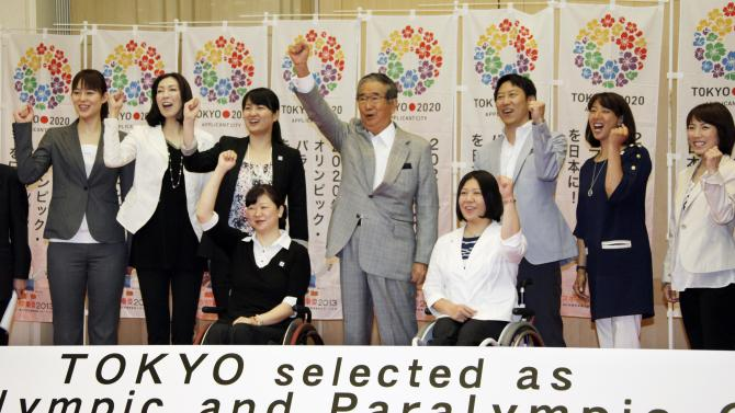 Tokyo Gov. Shintaro Ishihara, center, chairman of Tokyo 2020 Council, shows his spirit with Japanese Olympians and Paralympians during a press conference in Tokyo Thursday, May 24, 2012, after learning the Japanese capital was selected among the three finalists in the announcement of 2020 Olympic and Paralympic Games candidate cities in Quebec City, Canada. They are: Paralympians, swimmer Mayumi Narita, front left, and chair skier Kuniko Obinata, front right, and Olympians, from left, volleyball players, Kana Oyama and Motoko Obayashi, swimmers, Ai Shibata and Daichi Suzuki, synchronized swimmer Mikako Kotani and short track speed skater Ikue Teshigawara. (AP Photo/Koji Sasahara)