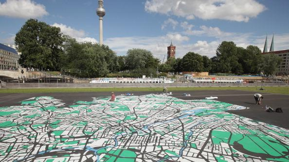 Landscape architect Lisa Hankow paints a giant map of Berlin in the city center the broadcast tower at Alexanderplatz and City Hall (R) on August 6, 2012 in Berlin, Germany. The map, which will measure 50 meters X 50 meters when finished, is in the scale of 1:775 and is an art installation meant to coincide with 775th anniversary of Berlin, which the city will celebrate in October. (Photo by Sean Gallup/Getty Images)