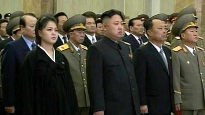 FILE - In this Dec. 17, 2012 file image made from video, North Korean leader Kim Jong Un, second from left in front row, and his wife Ri Sol Ju, left, attend a ceremony to reopen the mausoleum where his father's embalmed remains will lie in state, as they mark the first year of his death in Pyongyang, North Korea. The seemingly pregnant belly sported by the wife of North Korean leader Kim Jong Un in mid-December appeared to be gone by New Year's Day. That's sent South Korean media into a frenzy of speculation that there's a new baby in the ruling Kim dynasty. (AP Photo/KRT via AP Video, File) NORTH KOREA OUT, TV OUT