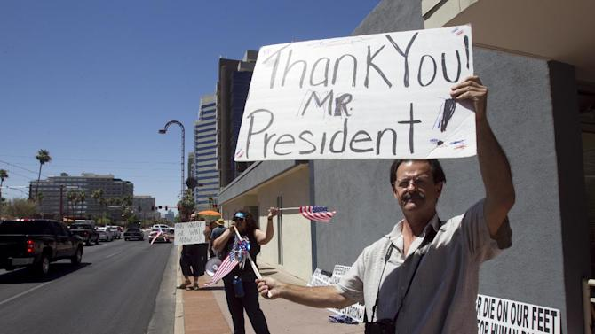 Nick Thomas, 53, of Phoenix holds a sign thanking President Obama at the Arizona Democratic Party in Phoenix. President Barack Obama is easing enforcement of immigration laws, effective immediately. The new policy offers a chance for hundreds of thousands of younger illegal immigrants to stay in the U.S. and work. (AP Photo/The Arizona Republic, Carlos Chavez)  MARICOPA COUNTY OUT; MAGS OUT; NO SALES