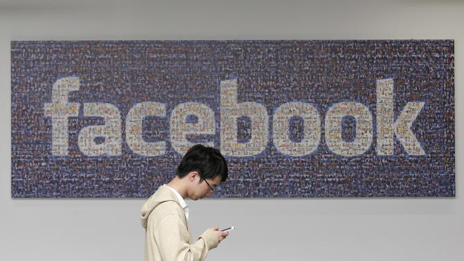 FILE - In this June 11, 2014 photo, a man walks past a Facebook sign in an office on the Facebook campus in Menlo Park, Calif. Facebook's recent effort to force people to adopt its standalone mobile messaging app has privacy-concerned users up in arms. In truth, Facebook Messenger isn't any more invasive than Facebook's main app _or other similar applications. (AP Photo/Jeff Chiu, File)