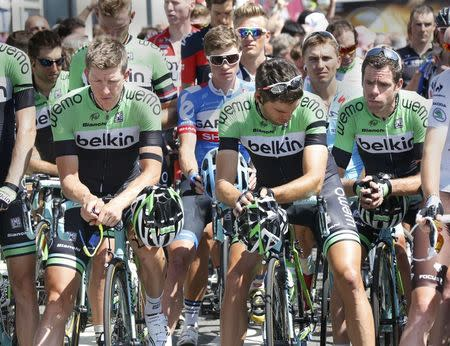 Riders of the Dutch cycling team Belkin wear black armbands and observe a minute of silence before departing on the 13th stage of the Tour de France cycle race