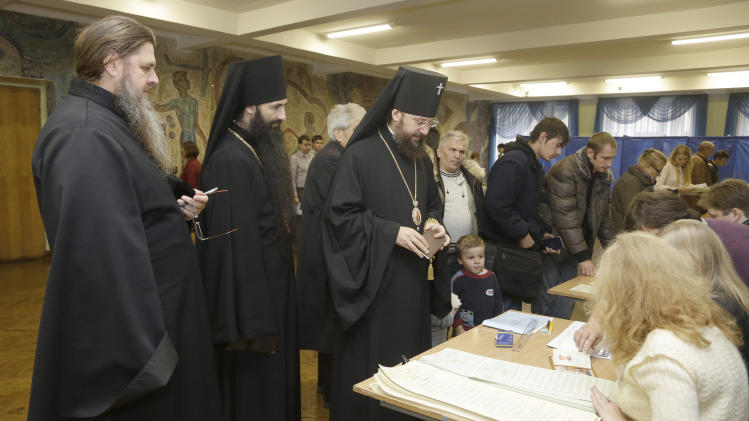 Orthodox priests receive their ballot papers at a polling station in Kiev, Ukraine, Sunday, Oct. 28, 2012. Voters in Ukraine are choosing a new parliament. (AP Photo/Efrem Lukatsky)