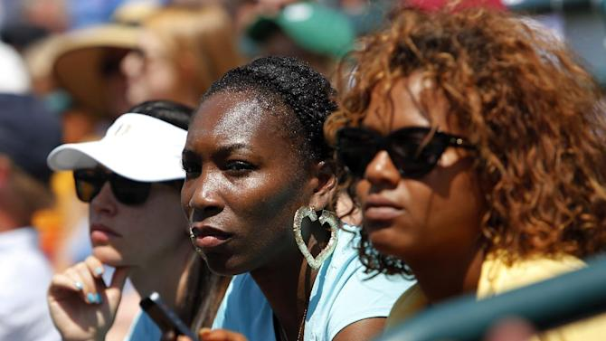 Venus Williams, center, watches her sister, Serena Williams, play Jelena Jankovic, of Serbia, during the singles final at the Family Circle Cup tennis tournament in Charleston, S.C., Sunday, April 7, 2013.  Williams defeated Jankovic, 3-6, 6-0, 6-2, to win the Family Circle Cup. (AP Photo/Mic Smith)