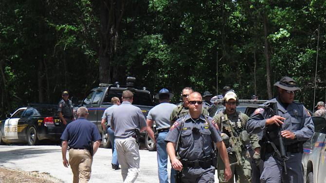 ALTERNATE CROP OF RPAS102-- FBI agents and Mississippi state troopers prepare to search for a man charged with kidnapping a Tennessee mother and her three daughters and killing two of them, Wednesday, May 9, 2012 in Guntown, Miss.  The Mississippi man, Adam Mayes, 35, was added Wednesday to the FBI's 10 Most Wanted list. (AP Photo/Adrian Sainz)