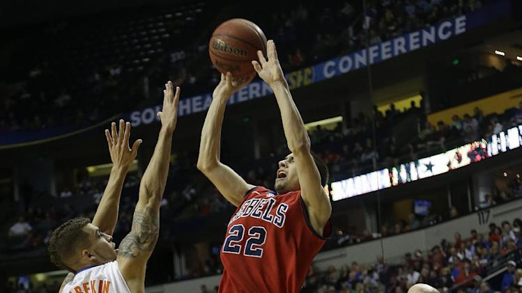 Mississippi guard Marshall Henderson (22) shoots a 3-point shot over Florida guard Scottie Wilbekin (5) as Mississippi head coach Andy Kennedy looks on during the second half of an NCAA college basketball game in the final round of the Southeastern Conference tournament, Sunday, March 17, 2013, in Nashville, Tenn. (AP Photo/Dave Martin)