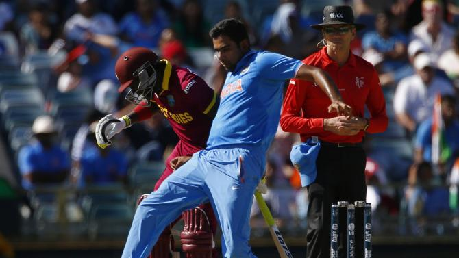 India's Ravichandran Ashwin attempts to field the loose ball with his feet off West Indies batsman Jonathan Carter during their Cricket World Cup match in Perth
