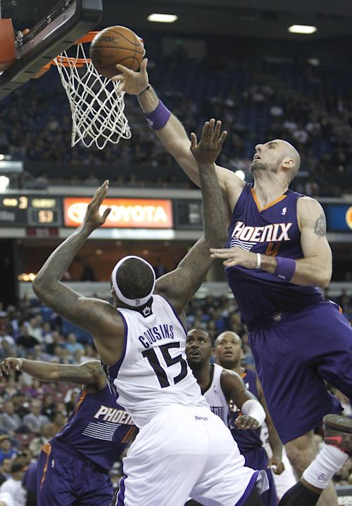 Sacramento Kings center DeMarcus Cousins goes to the basket against Phoenix Suns Marcin Gortat, of Poland, right, during the third quarter of an NBA preseason basketball game in Sacramento, Calif., Th