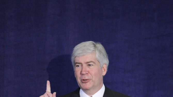 FILE - In this April 27, 2011 file photo, Michigan Gov. Rick Snyder delivers an address at a United Way office in Detroit on changes he wants to see in education. A proposal that Snyder commissioned to overhaul Michigan's education system would let students take their public funding to any district that will accept them, enroll in state-funded online learning courses and get $2,500 in scholarship money for each semester they graduate early from high school. (AP Photo/Carlos Osorio, File)