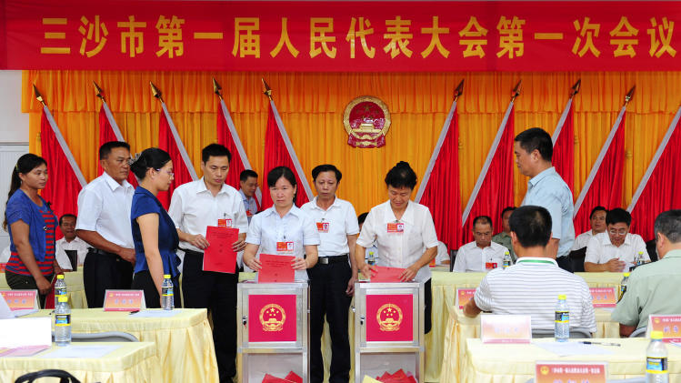 In this photo released by China's Xinhua News Agency, representatives cast their votes in the first session of the first Sansha Municipal People's Congress held on Yongxing Island, the government seat of Sansha City in south China's Hainan province Monday, July 23, 2012. China has rolled out the red carpet for its newest city, on a small, remote island in the South China Sea that is also claimed by Vietnam. Beijing on Tuesday, July 24, formally established the city of Sansha to bolster its claim on the sea's oil and gas-rich waters. The move is likely to anger China's neighbors and competing claimants in a dispute that has at times led to maritime standoffs. (AP Photo/Xinhua, Hou Jiansen) NO SALES