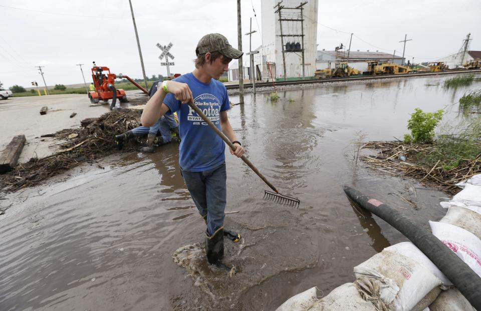 New Hartford firefighter Dakota Callan removes debris from a pump hose, Tuesday, June 25, 2013, in New Hartford, Iowa. Hundreds of residents obeyed an order to evacuate their homes in this northeast Iowa town Tuesday before floodwaters from a rising creek could strand them. (AP Photo/Charlie Neibergall)