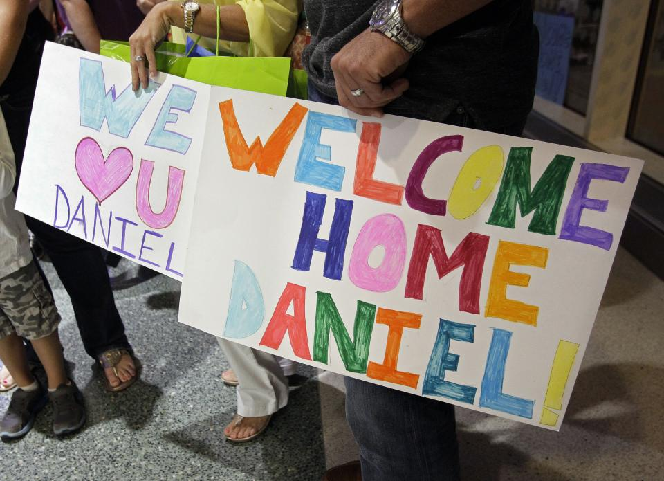 In this Saturday, Sept. 8, 2012 photo, friends hold signs as they await the arrival, from Guatemala City, of Ryan and Jessica Hooker, at McGhee Tyson Airport in Louisville, Tenn., with their newly adopted son Daniel and their daughter Ellyson. (AP Photo/Wade Payne)