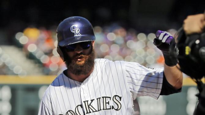 Colorado Rockies' Charlie Blackmon slides safe into third against the Arizona Diamondbacks during the third inning of a baseball game Saturday, Sept. 20, 2014, in Denver. (AP Photo/Jack Dempsey)