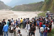 Villagers gather by the Seti river in Nepal after it burst its banks near Pokhara on May 5. A landslide caused by days of heavy rain had blocked the Seti near its source in the snow fields and glaciers of the Himalayas, said an army spokesman
