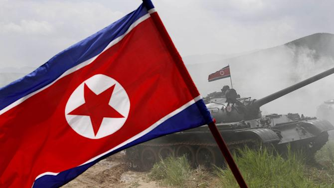 "FILE - In this July 27, 2012 file photo, a North Korean flag flutters during a military exercise by the historic 105 tank unit at an undisclosed location in North Korea, marking the 59th anniversary of the armistice that ended the 1950-53 Korean War. North Korea's military, founded 81 years ago Thursday, is older than the country itself. It began as an anti-Japanese militia and is now the heart of the nation's ""military first"" policy. Late leader Kim Jong Il elevated the military's role during his 17-year rule, boosting troop levels to an estimated 1.2 million soldiers, according to the South Korean government. The military's new supreme commander, Kim Jong Un, gave the Korean People's Army a sharpened focus this year by instructing troops to build a ""nuclear arms force."" (AP Photo/Jon Chol Jin, File)"