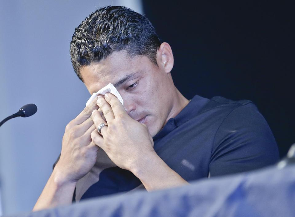 San Diego Padres shortstop Everth Cabrera, who was suspended by Major League Baseball for 50 games, wipes his tears after breaking down while addressing the media during a news conference in San Diego, Monday, Aug. 5, 2013. (AP Photo/Lenny Ignelzi)