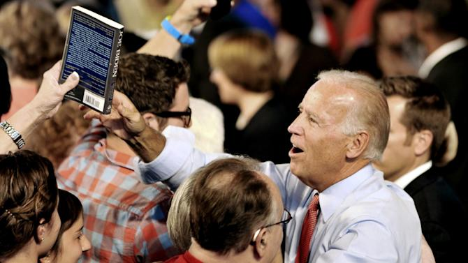 """Vice President Joe Biden greets supporters as one hands him a copy of the book """"Joe Biden"""" after he addressed a grassroots rally, Tuesday, Aug. 21, 2012, in Minneapolis. (AP Photo/Jim Mone)"""