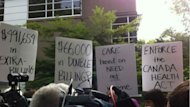 Dozens of protesters brandished signs outside the Cambie Surgical Centre on Monday.