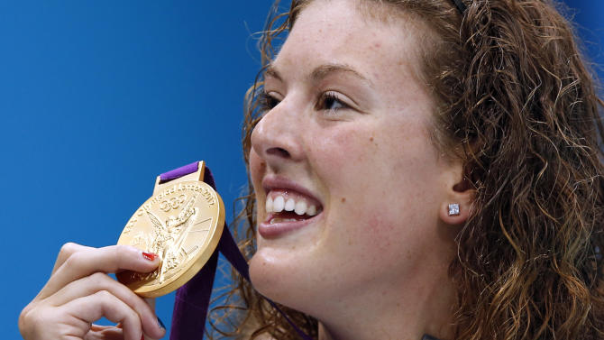 FILE - In this July 31, 2012, file photo, United States' Allison Schmitt holds her gold medal aloft after winning the women's 200-meter freestyle swimming final at the Aquatics Centre in the Olympic Park during the 2012 Summer Olympics in London. One week, you're basking in the glory, five medals around your neck. The next, you're adjusting to the rigors of studying and exams. For Schmitt, one of the top U.S. athletes at the London Games, it's back to school. (AP Photo/Daniel Ochoa De Olza, File)