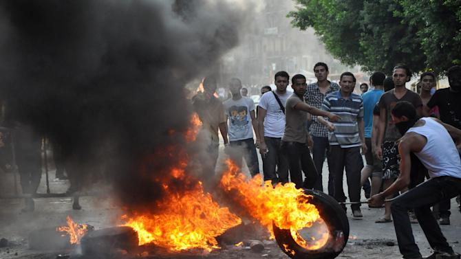 Egyptian protesters burn tires as they clash with riot police, unseen, outside the U.S. embassy in Cairo, Egypt, early Thursday, Sept. 13, 2012, as part of widespread anger across the Muslim world about a film ridiculing Islam's Prophet Muhammad. (AP Photo/Hussein Tallal)