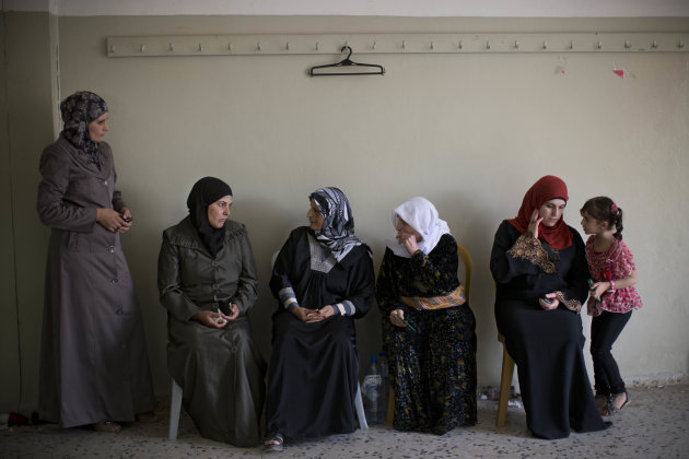 CAPTION CORRECTION, CORRECTS BYLINE IN CAPTION - Palestinian women wait to cast their vote at a polling station in the West Bank town of Kabatyeh, near Jenin, Saturday, Oct. 20, 2012. Palestinians voted for mayors and local councils in 93 communities across the West Bank on Saturday--their first chance to cast ballots in six years. (AP Photo/Bernat Armangue)