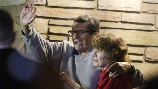 """FILE - In this Nov. 9, 2011 file photo, former Penn State Coach Joe Paterno and his wife, Sue Paterno, stand on their porch to thank supporters gathered outside their home in State College, Pa.  Breaking more than a year of silence, Sue Paterno is defending her late husband as a """"moral, disciplined"""" man who never twisted the truth to avoid bad publicity. The wife of the former Penn State coach is fighting back against the accusations against Joe Paterno that followed the Jerry Sandusky scandal. Her campaign started with a letter sent Friday Feb. 8, 2013, to former Penn State players. (AP Photo/Gene J. Puskar, File)"""