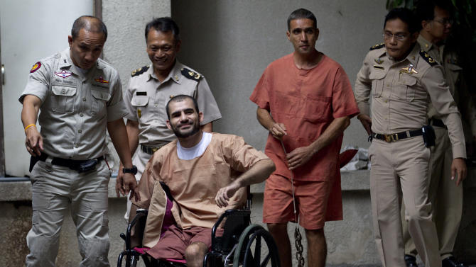 Two Iranian suspect bombers, Saeid Moradi, center left, and Mohammad Kharzei, center right, leave the criminal court in Bangkok, Thailand, Thursday, Aug. 22, 2013. A Thai court sentenced Thursday Moradi, 29, to life in prison for attempting to murder a police officer and possessing explosives that damaged property and injured several civilians. It sentenced Mohammad Kharzei, 43, to 15 years in jail for possessing explosives.(AP Photo/Sakchai Lalit)