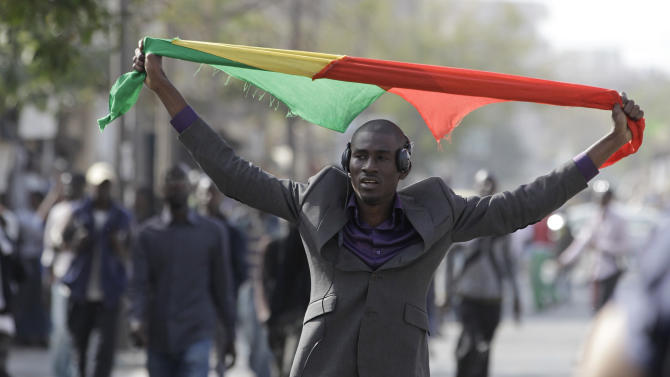 An anti-government protester carries a Senegalese flag as he walks near a central square that protesters had planned to occupy before being rebuffed by police, in central Dakar, Senegal Thursday, Feb. 16, 2012. Police used tear gas and rubber bullets to disperse demonstrators who had planned to go ahead with a sleep-in Thursday at Place de l'Obelisque, even though the government had banned the demonstration being held one week before the country's presidential election. (AP Photo/Rebecca Blackwell)