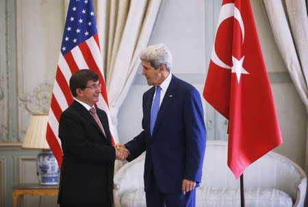 U.S. Secretary of State Kerry shakes hands with Turkish Foreign Minister Davutoglu in Paris