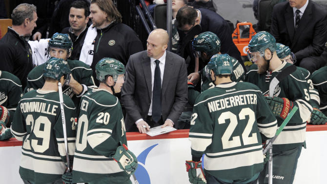 Minnesota Wild head coach Mike Yeo, center, diagrams a play of Wild players Jason Pominville (29), Ryan Suter (20), Nino Niederreiter (22), of Switzerland and Christian Folin (5), of Sweden, during a timeout in the third period of an NHL hockey game against the Dallas Stars, Tuesday, Feb. 9, 2016, in St. Paul, Minn. (AP Photo/Tom Olmscheid)