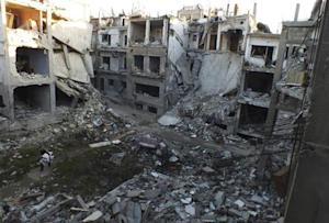 A man walks along a street lined with damaged buildings in the besieged area of Homs