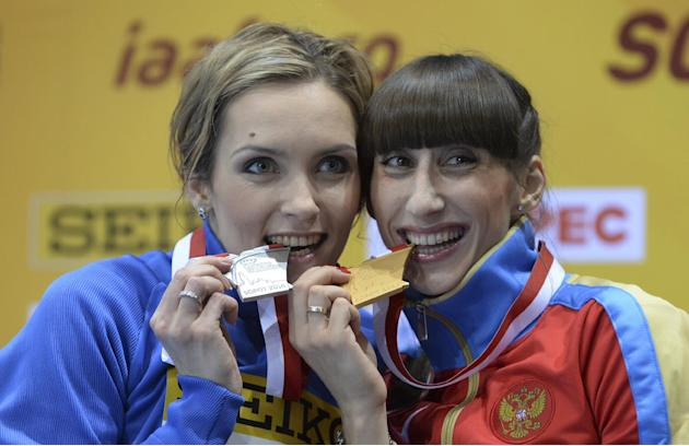 Ukraine's silver medal winner Olha Saladuha, left, and Russia's gold medal winner Ekaterina Koneva bite their medals during the ceremony for the women's triple jump during the Athletics In