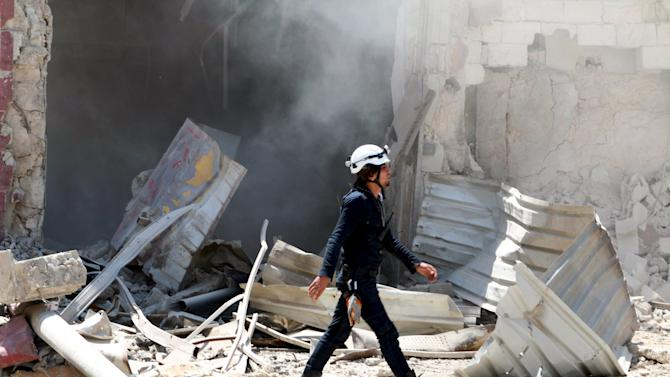 A Civil Defence member inspects a damaged site after what activists said was a barrel bomb dropped by forces loyal to Syria's president Bashar Al-Assad in Al-Shaar nighbourhood of Aleppo