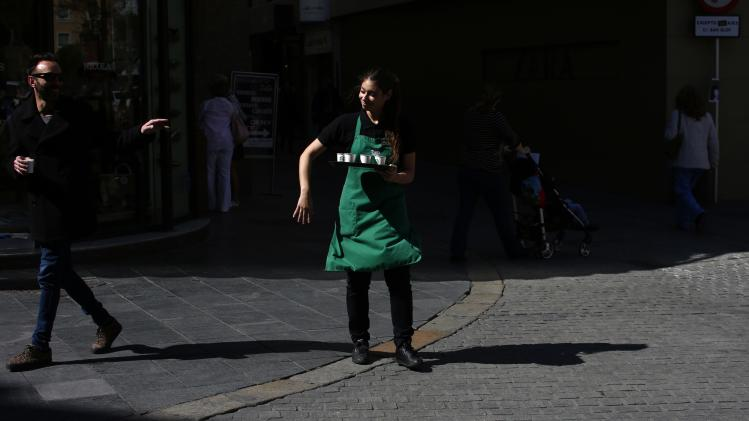 A woman holds a tray filled with cups of coffee in Seville