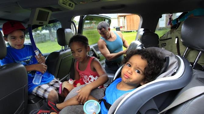Estanislao Fabian loads the their car as Jordan Fabian, 6, and Jaylah Cole, 6, comfort Jaden Fabian, 1, as they evacuate their home in advance of Tropical Storm Isaac, which is expected to make landfall in the region as a hurricane this evening in Plaquemines Parish, La.,  Tuesday, Aug. 28, 2012. Forecasters at the National Hurricane Center warned that Isaac, especially if it strikes at high tide, could cause storm surges of up to 12 feet (3.6 meters) along the coasts of southeast Louisiana and Mississippi and up to 6 feet (1.8 meters) as far away as the Florida Panhandle. (AP Photo/Gerald Herbert)