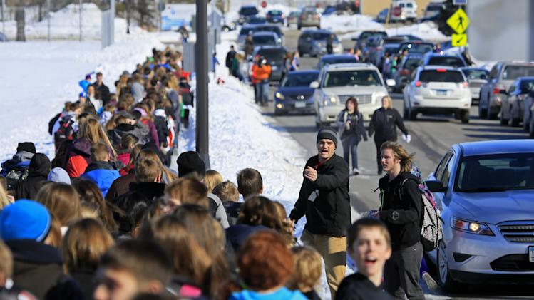 """Students are ushered back to New Prague Middle School in New Prague, Minn., Wednesday, March 20, 2013 after the all clear was issued followinga scare, after authorities responded  to a 911 call concerning an """"active shooter"""" at the middle school, but a staff member later said everyone is safe and there is no danger inside the building. The 911 call in which a caller claimed several people had been gunned down at the school was likely a hoax, Scott County Sheriff Kevin Studnicka said  said Wednesday. (AP Photo/The Star Tribune, Brian Peterson)  MANDATORY CREDIT; ST. PAUL PIONEER PRESS OUT; MAGS OUT; TWIN CITIES TV OUT"""
