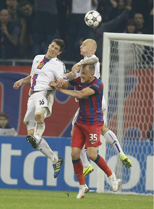 Basel's Fabian Schaer, left, and Ivan Ivanov, right, struggle for the ball with Steaua's Pantelis Kapetanos, bottom right, during the UEFA Champions League group E soccer match between Steaua Buchares