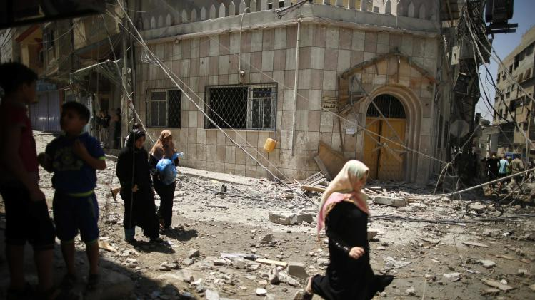 Palestinians walk past damaged mosque, which witnesses said was hit by Israeli shelling, in Gaza City