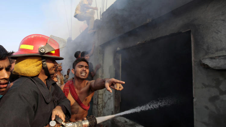 Bangladeshi firefighters and volunteers work to douse a fire at a two-storied garment factory in Dhaka, Bangladesh, Saturday, Jan. 26, 2013. The fire swept killed at least six female workers and injured another five, police and fire officials said. The latest fire occurred more than two months after a deadly fire killed 112 workers in another factory near the capital city, raising questions about the safety measures in Bangladesh garment industry. (AP Photo/A.M. Ahad)