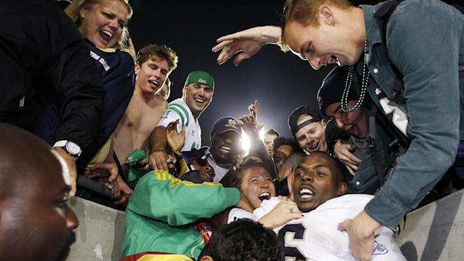Notre Dame running back Theo Riddick celebrates with fans after Notre Dame Southern California 22-13 in an NCAA college football game, Saturday, Nov. 24, 2012, in Los Angeles. (AP Photo/Danny Moloshok)