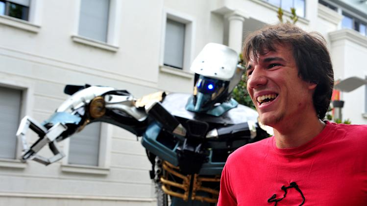 In this picture taken on Wednesday, July 23, 2014, Danilo Baletic, the 22-year-old art student smiles by a towering figure, mostly made of old car parts and other waste in Podgorica, Montenegro. Giant scrap-metal sculptures of popular Autobots, Decepticons and the evil Megatron himself are on show at several locations in the Montenegrin capital of Podgorica _ work of a young artist who saw a new role for his childhood heroes. (AP Photo/Risto Bozovic)