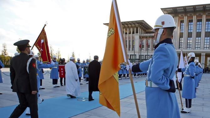 Pope Francis and Turkey's President Erdogan walk in front of honor guard at the presidential palace in Ankara