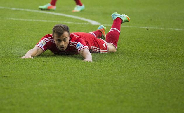 Bayern's Xherdan Shaqiri of Switzerland lies on the ground during the German Bundesliga soccer match between VfL Wolfsburg and Bayern Munich inWolfsburg, Germany, Saturday, March 8, 2014