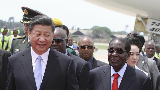 Chinese President Xi Jinping walks with Zimbabwean President Robert Mugabe on arrival for a state visit in Harare, Zimbabwe