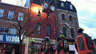 A two-alarm fire has closed a section of Queen Street West to traffic and sent one person to hospital with serious burns.