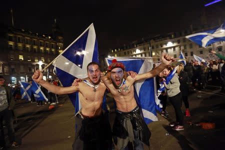 Yes campaign supporters wave Scottish Saltire flags in central Glasgow